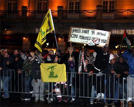Her vises et større bildeutsnitt av demonstrantene, som også holdt opp to Hizbollah-flagg, et skjerf fra Algerie og et Palestina-flagg.