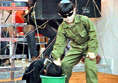 To barnehagebarn fremstiller en situasjon hvor en israelsk soldat torturerer en palestinsk fange.