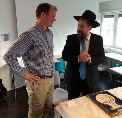 Rabbiner Shaul Wilhelm forklarer symbolikken i statuetten som ble overrakt Conrad Myrland. (Foto: Privat)