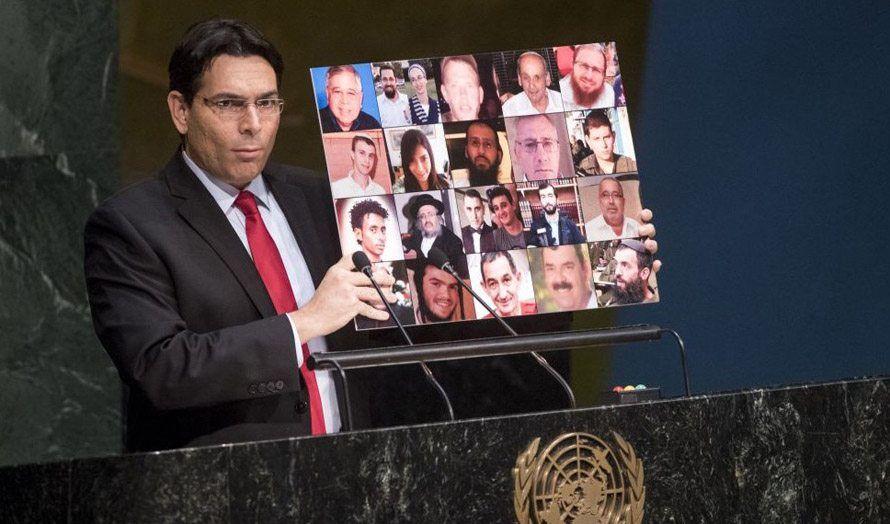 Israels FN-ambassadør Danny Danon holdt opp plakat med bilder av høstens israelske terrorofre for FNs generalforsamling, som mandag kun ville fordømme Israel. (Foto: FN)