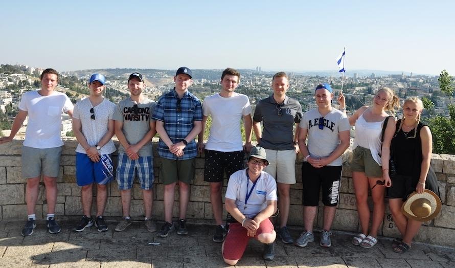 Gruppa poserer med Jerusalem i bakgrunnen. På huk foran er den israelske guiden Yoni Zierler. (Foto: Kjetil Ravn Hansen)